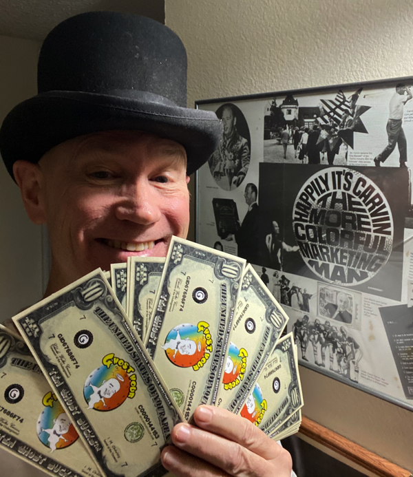 Carvin believes that to get user loyalty portal providers should share their revenues with their users. Here James Carvin holds up a fist full of Ǥhost Bucks.